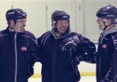 Hockey Alberta's February Coach of the Month, Jason Oakey (middle), shares a laugh his fellow coaches during practice.