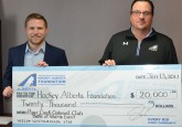 Piper Creek Optimist Club President Kevin Walsh (left) presented Hockey Alberta Foundation Executive Director Tim Leer with a cheque for $20,000 for the Every Kid Every Community program.