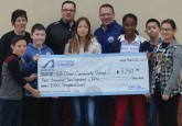 From left: G.H. Dawe Community School Principal Sue Carmichael, Executive Director of the Hockey Alberta Foundation Tim Leer, and Math/Gym teacher Daryl Puzey stand with a handful G.H. Dawe students as the Foundation presents a grant through the Every Kid