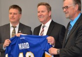 Joel Ward (centre), RDC President and CEO, receives a special Hockey Alberta jersey from Rob Litwinski, Hockey Alberta CEO and Terry Engen, Hockey Alberta Board Chair.