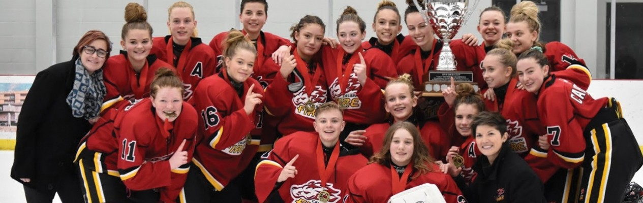 Head Coach of the Calgary Bantam Elite Fire Red, Kelsey Leifson (bottom right) celebrates a Wickfest championship with her team.